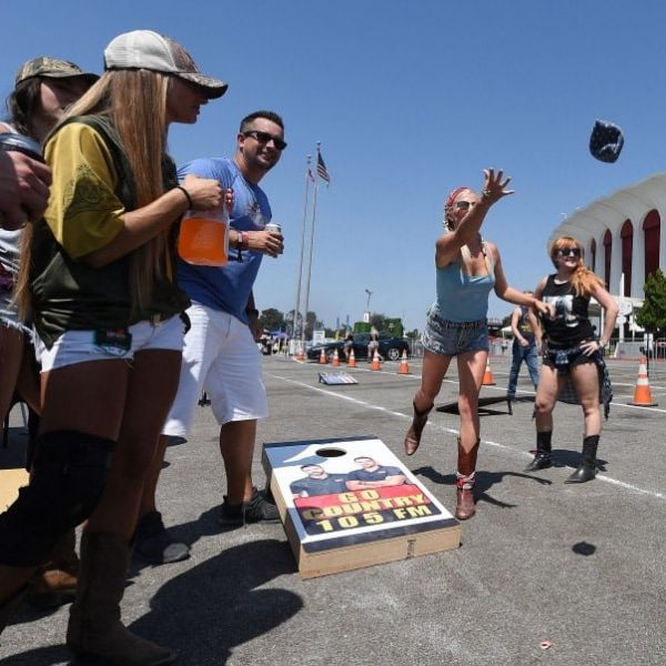 Country music fans MacKenzie Going, 30 from Redondo Beach, and Brandy Tutema, 28 from Torrence, play corn hole as they party at Tailgate Fest Saturday, September 1, 2018 in The Forum parking lot in Inglewood. Fans were able to stay at their vehicles and tailgate throughout the show. (Photo by Will Lester, Inland Valley Daily Bulletin/SCNG)